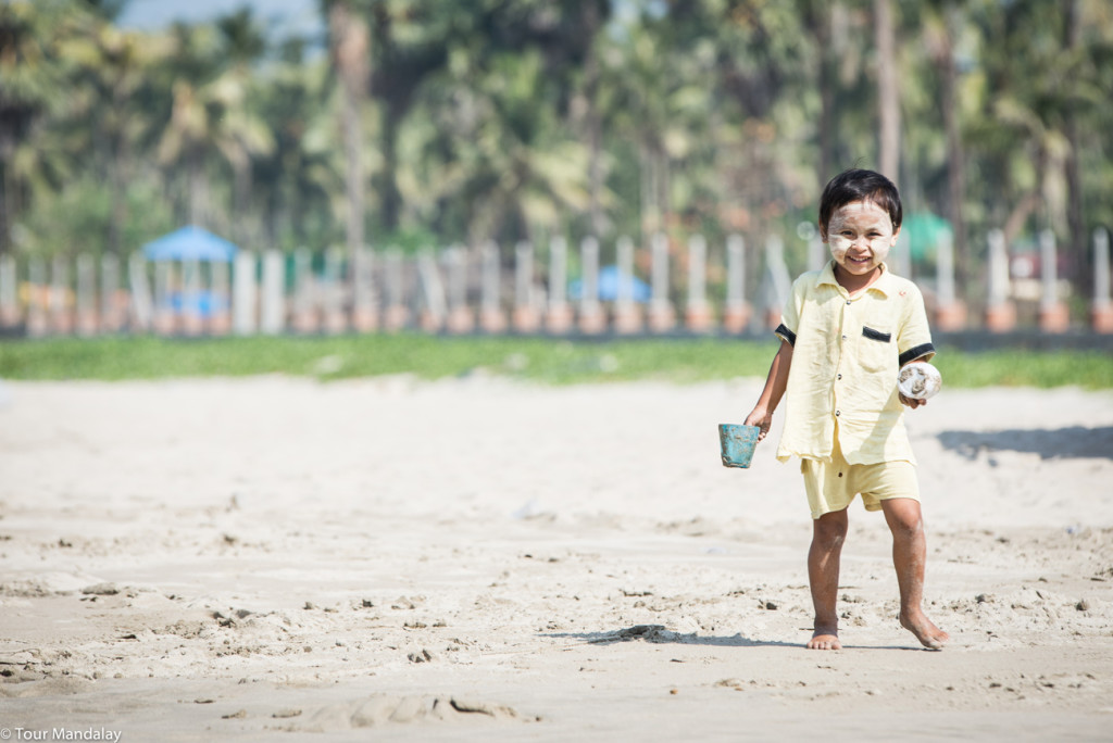 Child plays with sand on Ngwe Saung beach