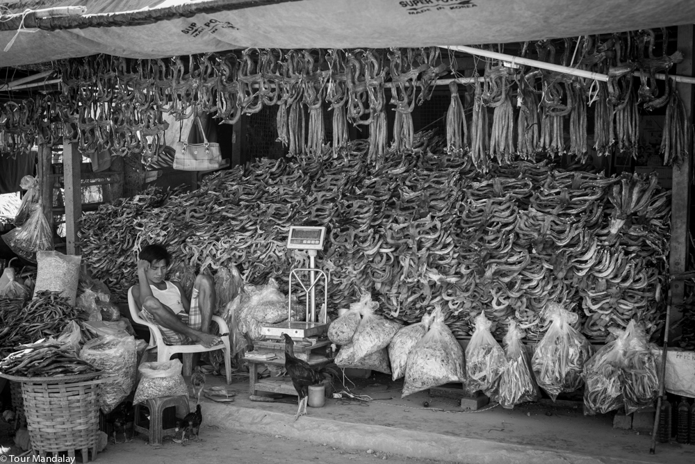 A man checks his phone next to a pile of dried fish