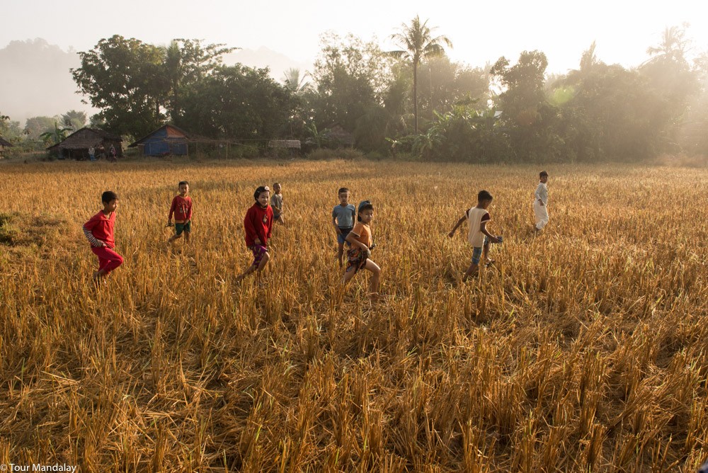 Children run across harvested fields to greet us