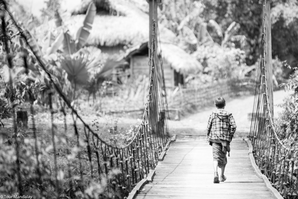A boy crosses one of Putao's many suspension bridges to the neighbouring village