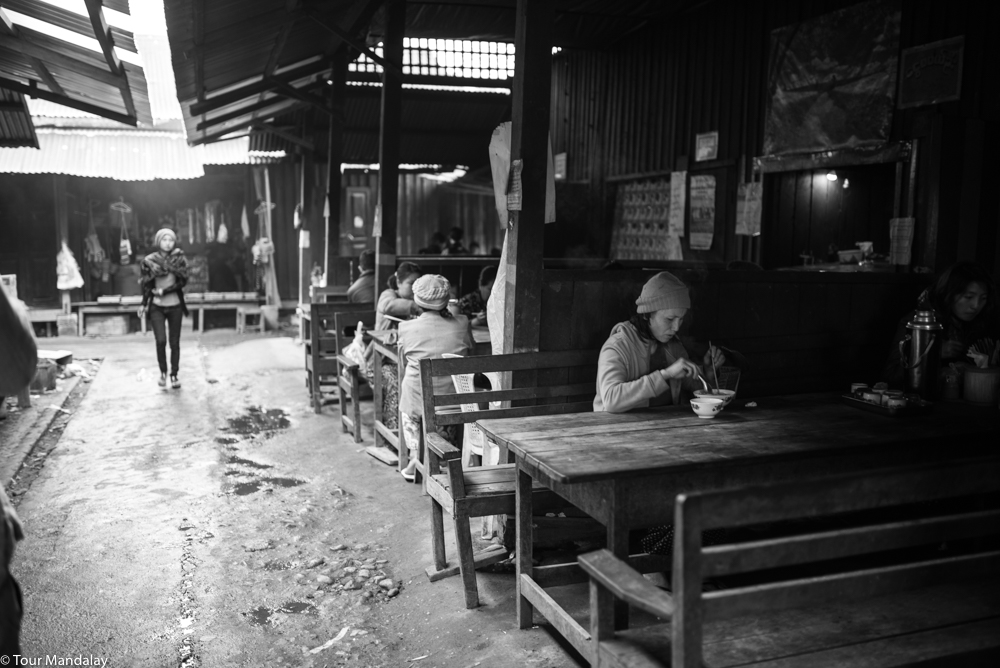 A lady tucks into a warm bowl of noodles at Putao's morning market