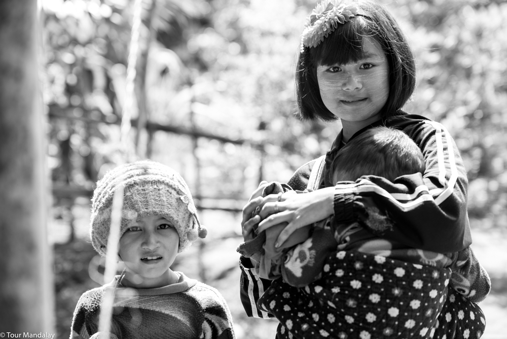 An older sister takes care of her siblings in a village located a stone's throw from Putao town